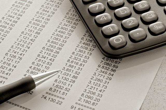 Pen-and-calculator-on-spreadsheet-budgets-accounting-close-budgeting-data-finance