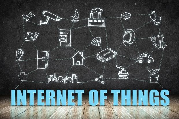 Internet of Things (IoT) word on wood floor with doodle icon on blackboard wall